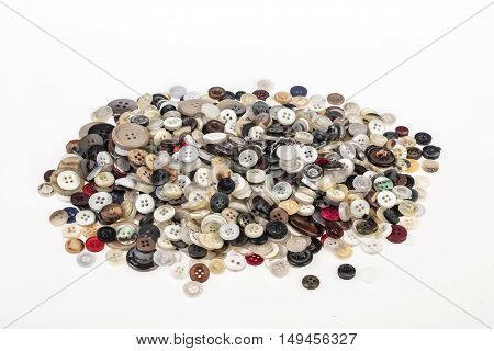 Many sewing buttons on an isolated studio background