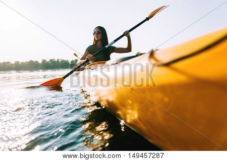 Looking for adventures. Low angle view of beautiful young smiling woman kayaking on lake and smiling
