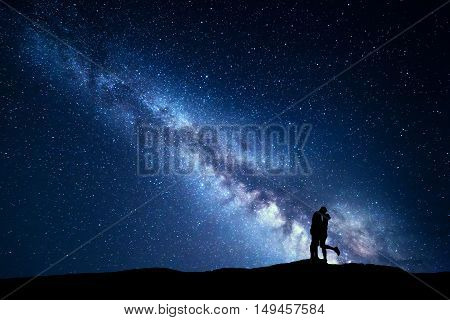 Milky Way. Night landscape with silhouettes of hugging and kissing man and woman on the mountain. Sky with stars. Silhouette of lovers. Couple relationship. Blue milky way with people. Universe