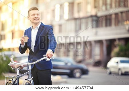 Coffee-to-go concept. Young man with bicycle and cup of coffee on street