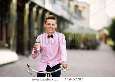 Young man in pink shirt holding cup of coffee and riding bicycle on street