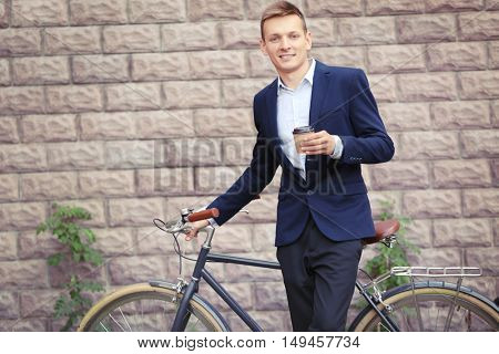Young man with bicycle and cup of coffee on brick wall background