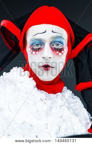 Close up portrait with cheerful clown in a vintage style with a typical makeup
