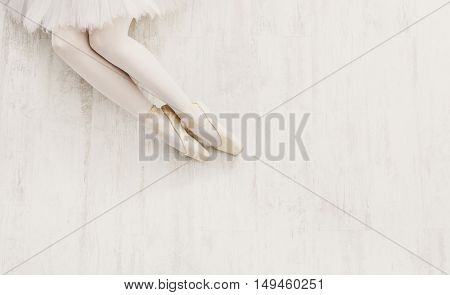 Ballet background. Closeup of young ballerina legs in pointe shoes on white wooden floor, top view from above with copy space. Ballet practice. Beautiful slim graceful feet of dancer.