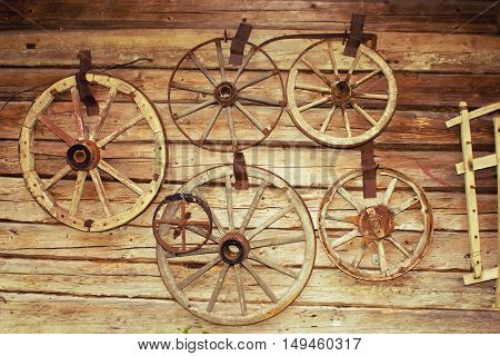 A lot of old vintage wheel of the coach or wagon. Cartwheel hang on the wall of an old house
