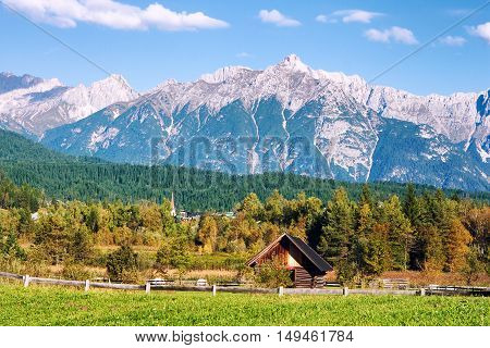 Idyllic tyrolean (Austria Europe) landscape with hills forest farm house blue sky and green fields.
