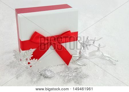 Christmas gift box with red bow, silver reindeer, white snowflake bauble and pine cone decorations on snow background.