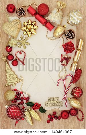 Red and gold christmas background border with tree decorations and baubles over light oak background on parchment paper.