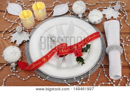 Christmas dinner table setting with white porcelain plates, bauble decorations, candles, cutlery, linen serviette, red ribbon and holly over oak background.
