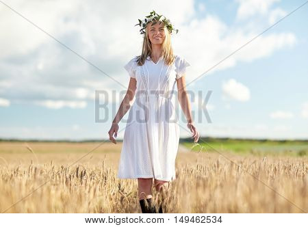 happiness, nature, summer holidays, vacation and people concept - happy smiling young woman or teenage girl in wreath of flowers and white dress on cereal field