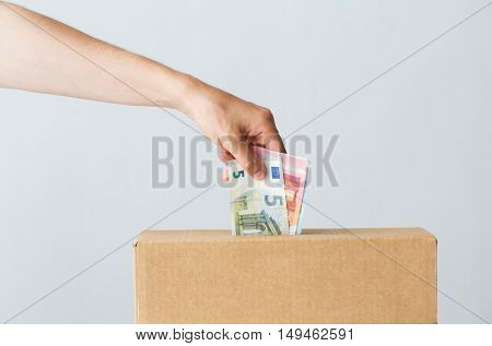 charity, finances, funding, investment and people concept - man putting euro money into donation box