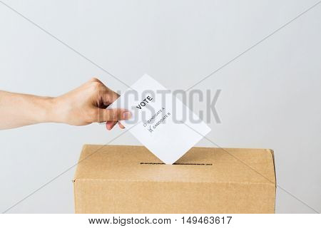 voting, civil rights and people concept - male hand putting vote with two candidates into ballot box on election
