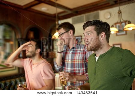 people, leisure, friendship and sport concept - upset male friends watching sport game or football match and drinking beer at bar or pub