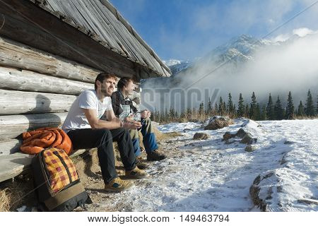 Two friends are relaxing on wooden bench in winter mountains outdoors