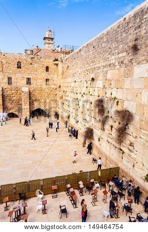 The area with tourists and pilgrims in front of the Western Wall in Jerusalem and Dome of the Rock in the background. Judaism. Israel.