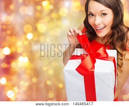 christmas, x-mas, valentines day, people and celebration concept - smiling woman in red dress with gift box over holidays lights background