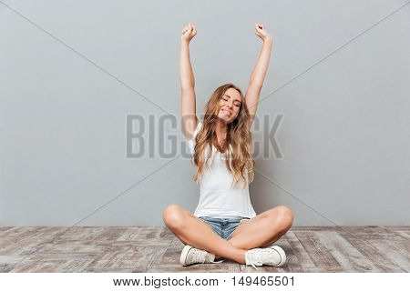 Portrait of a young woman stretching hands while sitting on the floor over gray background