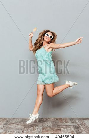 Full length of cheerful beautiful young woman in sunglasses jumping over gray background