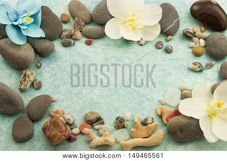 Abstract frame with stones, seashells and decorative flowers orchid on blue background