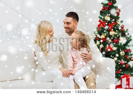 family, christmas, holidays and people concept - happy mother, father and little daughter sitting on sofa at home