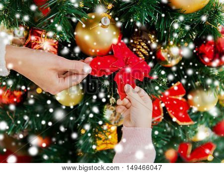 family, christmas, holidays, new year and people concept - close up of mother and child hands decorating christmas tree