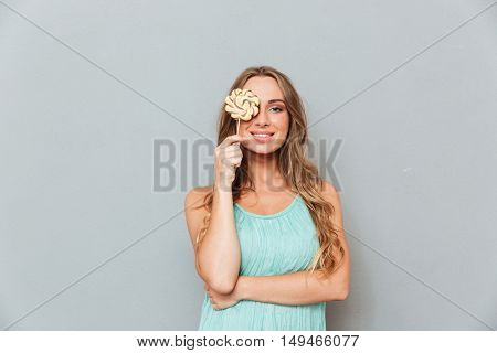 Smiling playful young woman covered her eye with lollipop over gray background