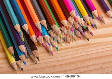 Wooden colorful pencils, on wooden table