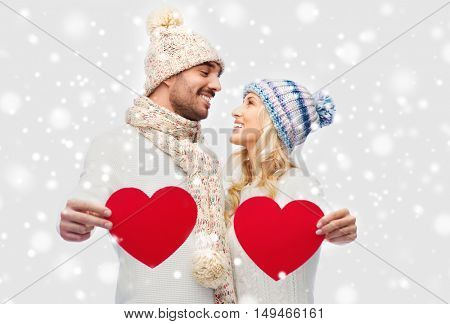 love, valentines day, couple, christmas and people concept - smiling man and woman in winter hats and scarf holding red paper heart shapes