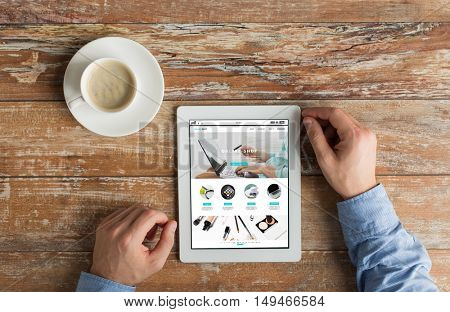 business, online shopping, people and technology concept - close up of male hands with internet shop page on tablet pc computer screen and coffee cup on wooden table