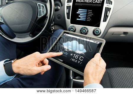 transport, business trip, technology, forecast and people concept - close up of male hands holding tablet pc computer with weather cast on screen in car