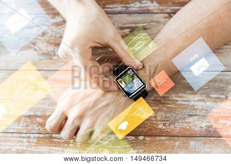 business, modern technology, media, internet and people concept - close up of male hands setting smart watch with news web page on screen on wooden table