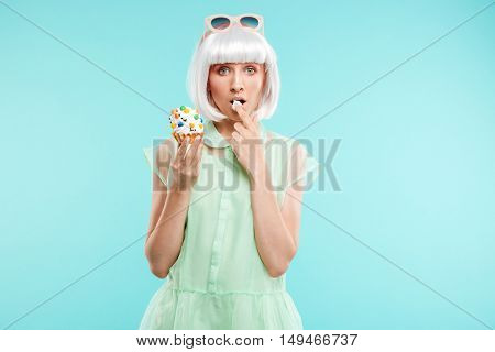 Pretty blonde young woman standing and tasting cupcake by finger over blue background