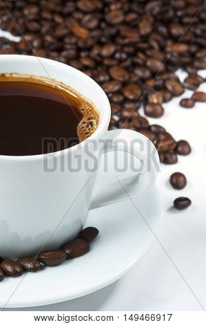 Cup of coffee with heap of coffee beans on white background. Cropped shot.