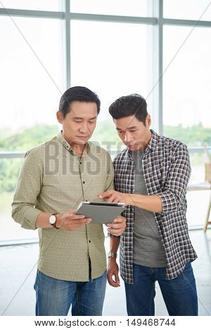 Vietnamese men discussing idea on tablet computer