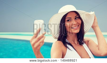 travel, summer, technology and people concept - sexy young woman taking selfie with smartphone over beach and swimming pool background