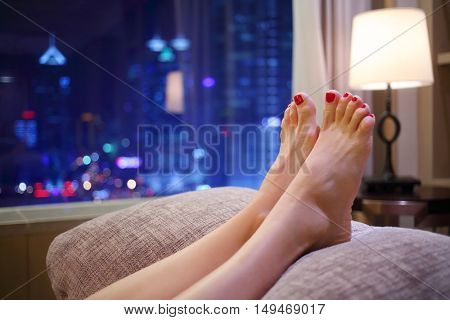 Woman puts her feet with red pedicure on pillow near window with city view