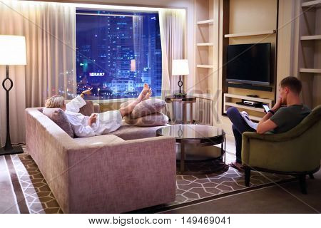 Couple get rest in sitting room near window with night city view