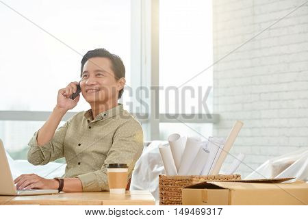 Smiling Asian businessman consulting customer on the phone