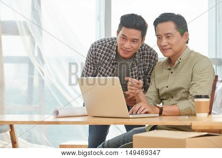 Asian businessman showing information on laptop screen to his colleague
