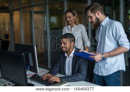 Team of colleagues working together on a computer.