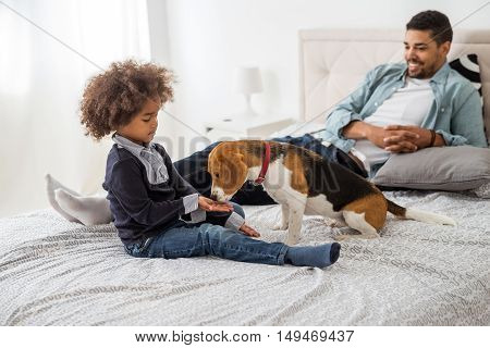 Cute african american girl feeding her dog.