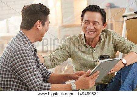 Vietnamese coworkers watching something on tablet computer