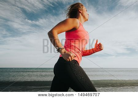 Blonde girl running in the beach. Close up view.
