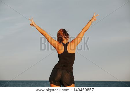 Blonde woman in sportswar raising arms and celebrating with victory sign with two hands. Back view.