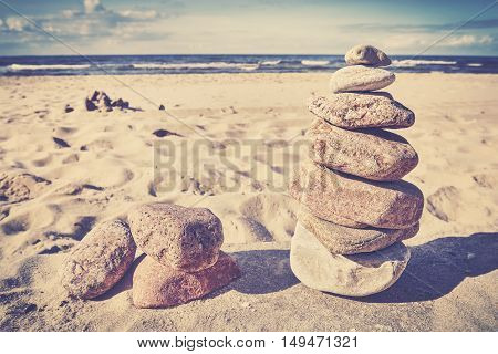 Vintage toned image of stones on a beach selective focus.