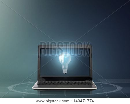 technology, idea and business concept - laptop computer with light bulb on screen over dark gray background