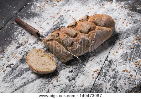 Baking and cooking concept background. Cut bread loaf with knife on rustic wood sprinkled with flour. Stained dirty surface of table.