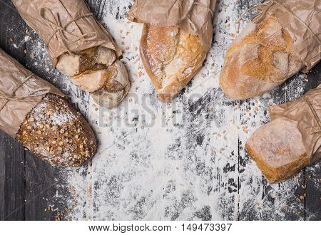 Baking and cooking concept background. Lots of different bread sorts, wrapped in craft paper top view with copy space in the middle on wooden table, sprinkled with flour.