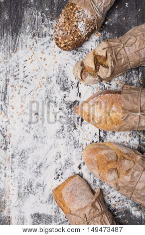 Baking and cooking concept background. Lots of different bread sorts, wrapped in craft paper top view with copy space on wooden table, sprinkled with flour. Vertical image