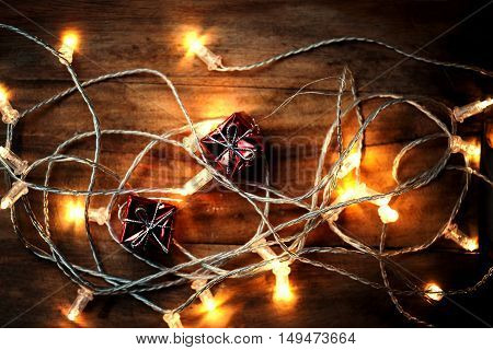 Christmas background greeting card with festive lights on dark wooden backdrop close up. Merry Christmas lights garland